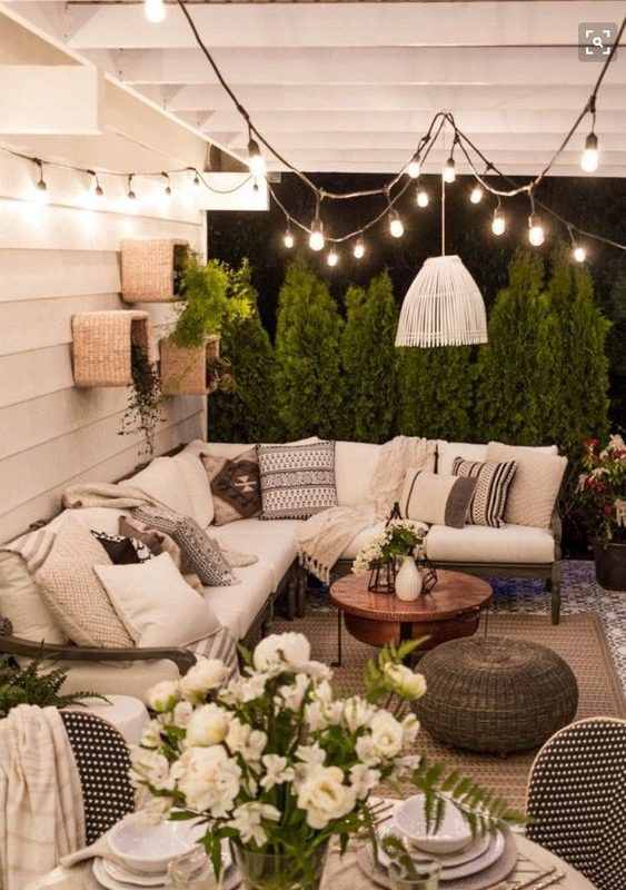 a boho patio with a large L-shaped sofa and a coffee table next to it plus wicker ottomans
