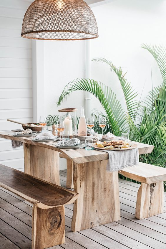 a boho tropical dining space with living edge wooden furniture and a wicker lampshade over the zone