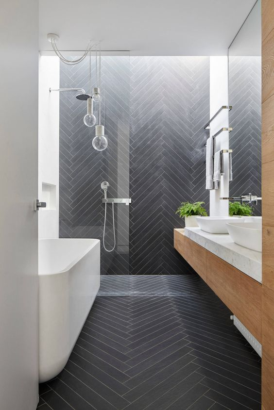 a contemporary bathroom clad with long and skinny graphite grey tiles in a chevron pattern