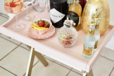 06 a genius IKEA hack to transform a tray table into an ultra-chic mini bar in blush is a very cute idea