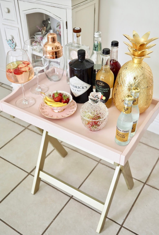 a genius IKEA hack to transform a tray table into an ultra-chic mini bar in blush is a very cute idea