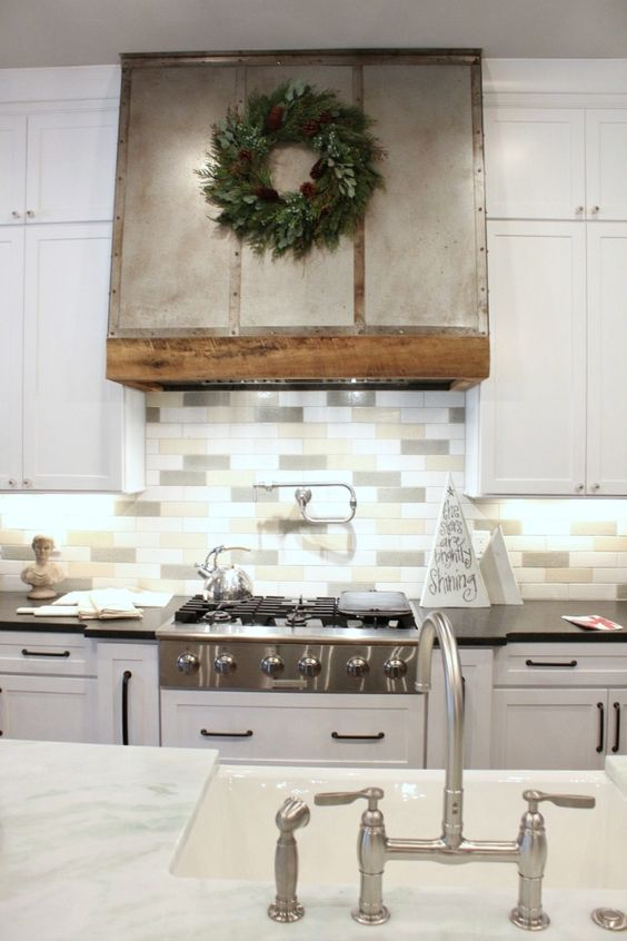 a modern farmhouse kitchen with white cabinets and a three tone skinny tile backsplash to add a touch of muted color