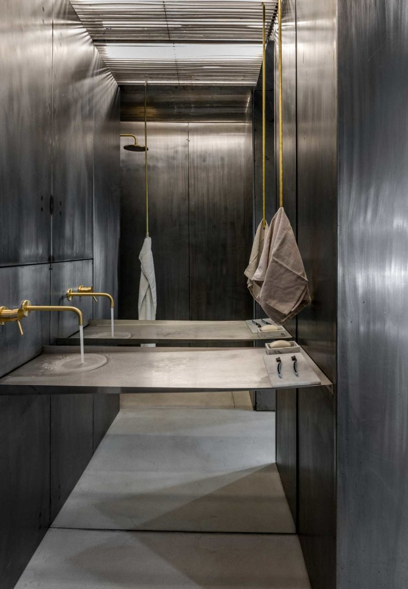 The bathroom is also clad with aged metal, too, there is gilded hardware, with a console with no separate sink and a shower space