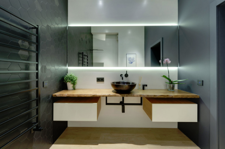 The bathroom is done with black hex tiles, sleek concrete walls, a floating vanity with storage and a lit mirror