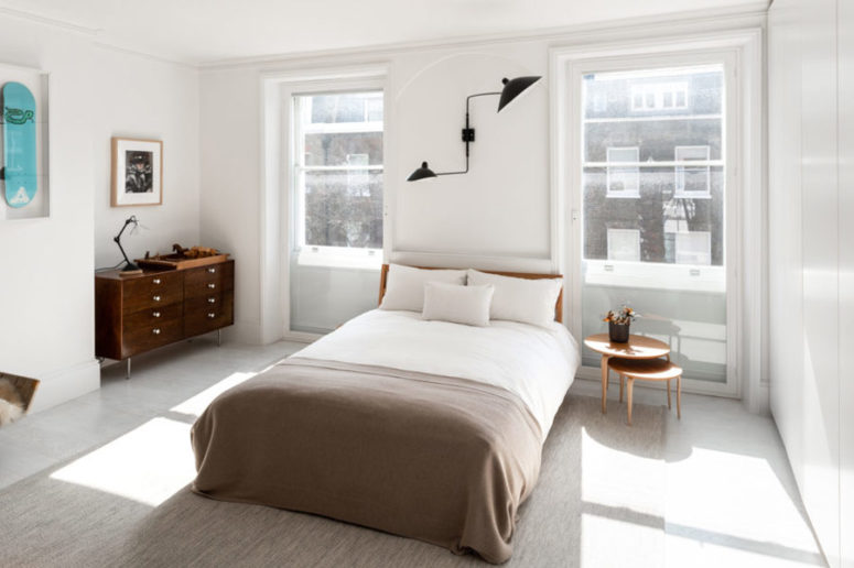 The bedroom features mid-century modern style, with comfy wooden furniture, bold artworks and a black metal lamp