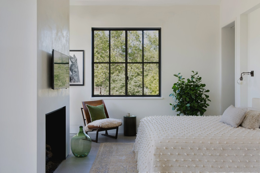 The master bedroom features a smaller window for more privacy, a fireplace, a bed and a chair with pillows and soft textiles