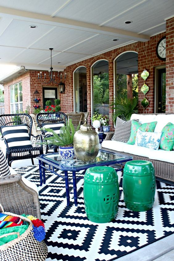 a super colorful patio done around a blue glass coffee table with various mismatching seating options