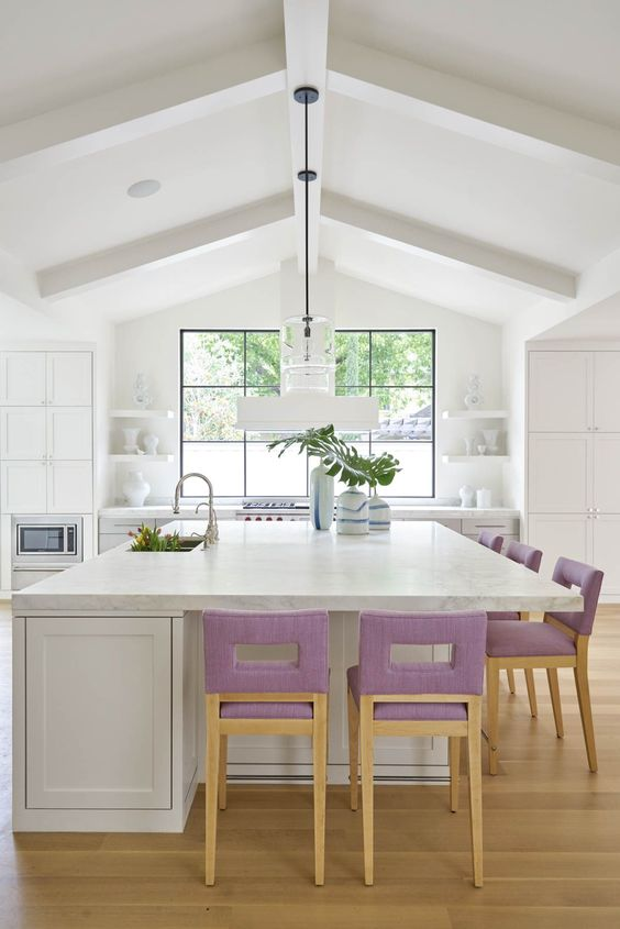 lilac upholstered stools add a touch of soft color to the neutral kitchen and make it cooler