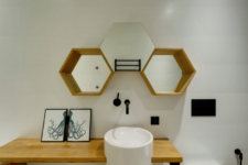 08 The powder room is done with hex mirrors, a sink on a wooden vanity