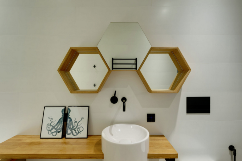 The powder room is done with hex mirrors, a sink on a wooden vanity