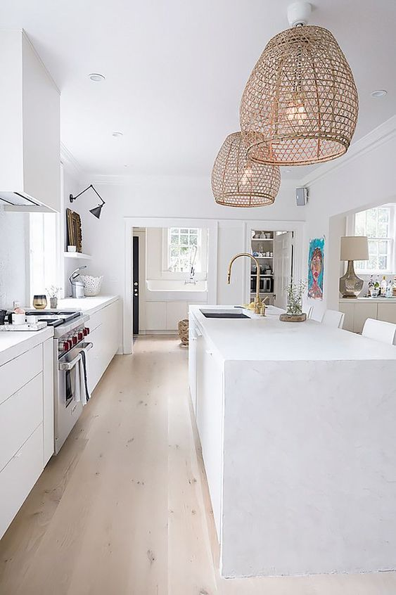 a pure white kitchen is given a rustic and outdoor feel with rattan lampshades over the kitchen island