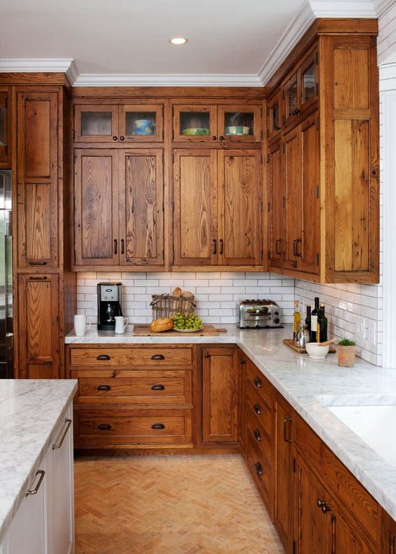 a rustic kitchen with warm-stained cabinets, white skinny tiles, white stoen countertops plus vintage handles