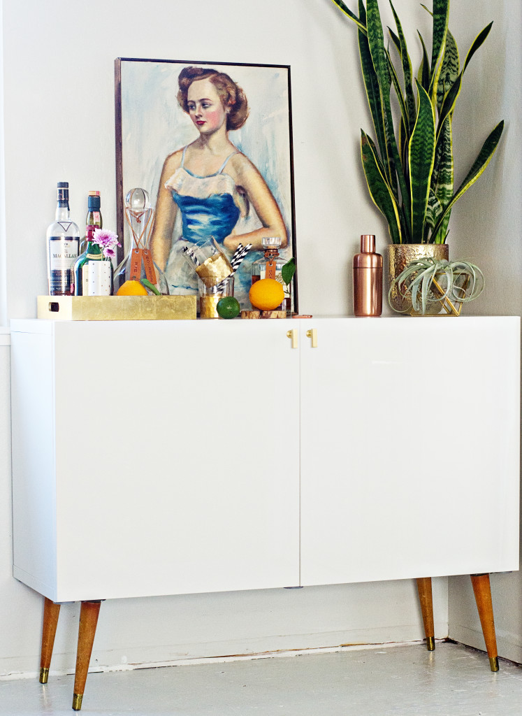 a stylish home bar in mid century modern style is made of an IKEA Besta unit on legs, everything is hidden inside for kid proofing