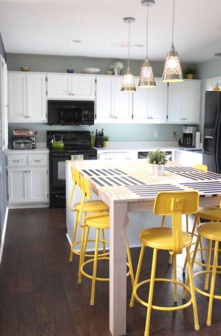 industrial and vintage bright yellow stools spruce up the neutral and blue kitchen and stand out a lot
