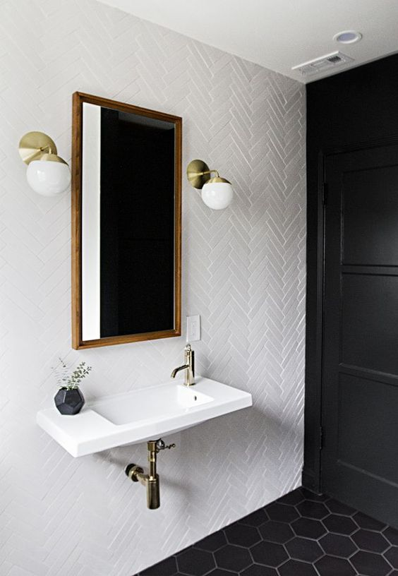 white skinny tiles in a  cheveron pattern paired with black hexagon tiles on the floor for a chic bathroom look