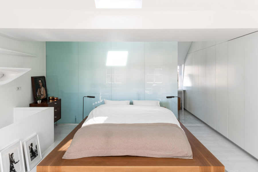 This bedroom is done with a blue glass wall, a platform bed, a rich stained dresser, black and white artworks