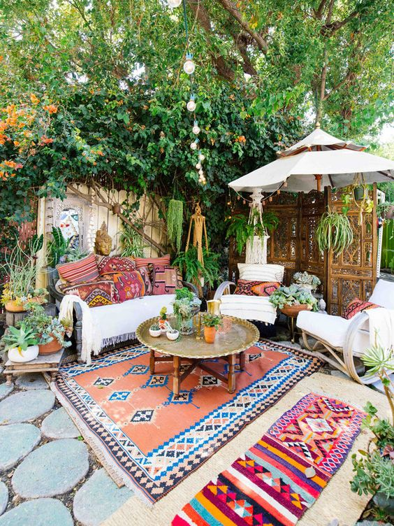 a colorful boho chic patio with a metal coffee table in the center and some seating furniture around it