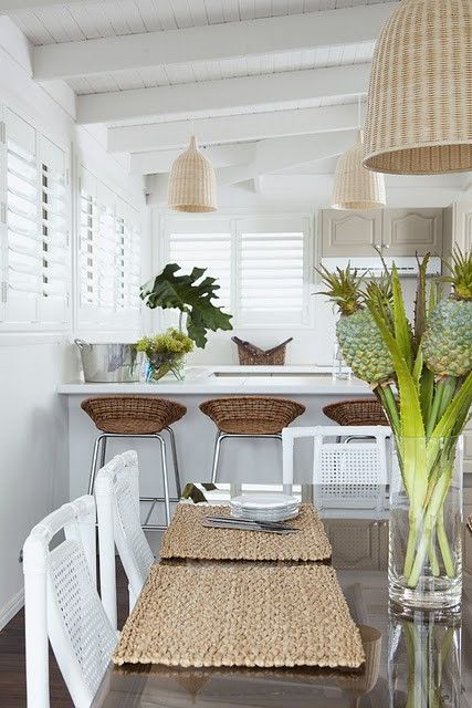 a tropical dining room with wicker lamps and stools in the breakfast zone plus some woven placemats