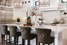 09 dark leather upholstered vintage inspired stools with ring pulls stand out in a neutral kitchen and add drama