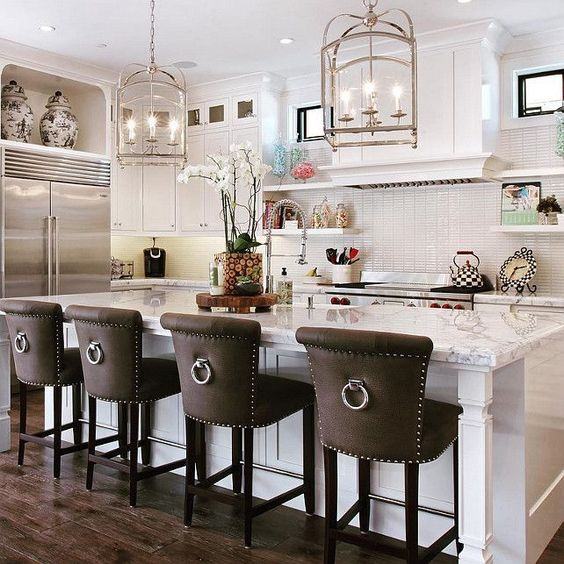 dark leather upholstered vintage inspired stools with ring pulls stand out in a neutral kitchen and add drama