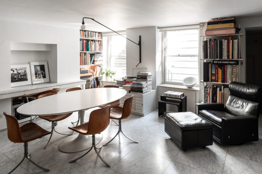 This is a shared home office with an oval table, leather chairs, a black chair and bookshelves all over