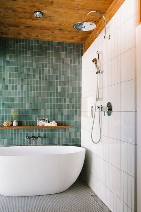 a bold contemproary bathroom with skinny white and mismatching green skinny tiles plus a grey mosaic tile floor