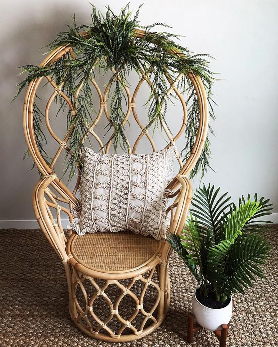 a catchy rattan peacock chair refreshed with interwoven greenery is a stylish idea with a modern twist