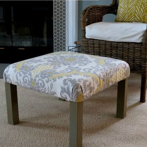 a living room ottoman made of an IKEA Lack table with printed grey and yellow fabric on top plus brown legs