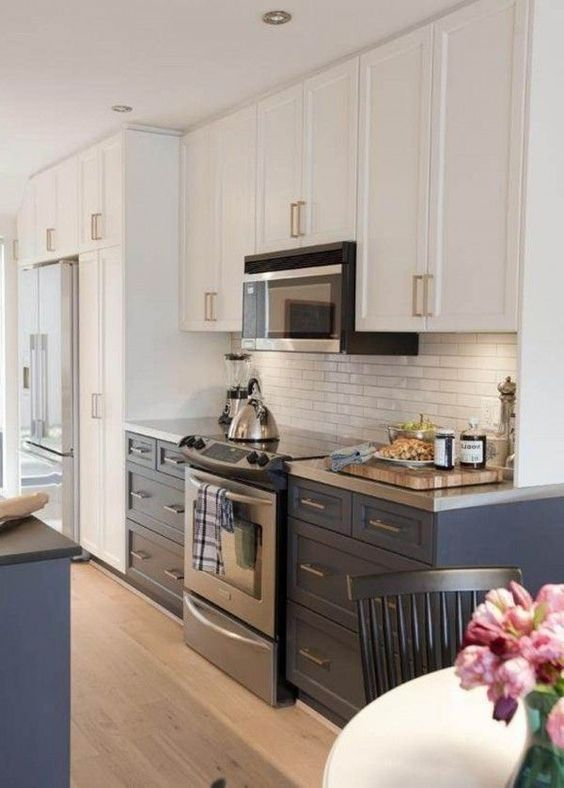 a two tone kitchen in navy and white with a white skinny tile backsplash and metal countertops for a bright and chic look