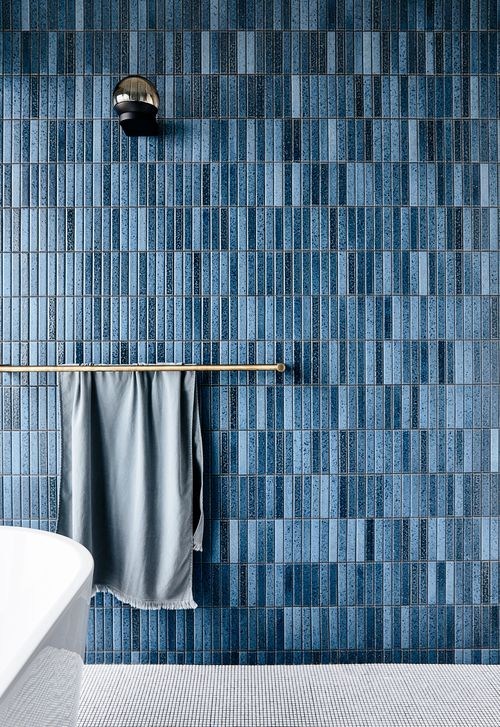 a chic contemporary bathroom with a grey floor, a blue navy skinny tile wall and brass touches looks chic
