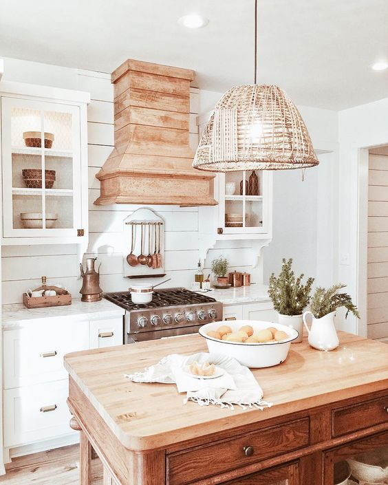 a vintage beach cottage kitchen with a wicker lampshade over the kitchen island for a more relaxed feel