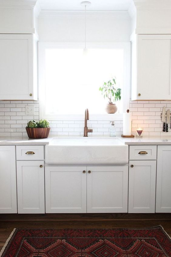 a white modern farmhouse kitchen with white skinny tiles and black grout on the backsplash and copper touches here and there