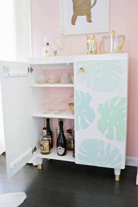 an IKEA Ivar cabinet turned into a stylish kid proof home bar with dimensional monstera leaves and gilded legs