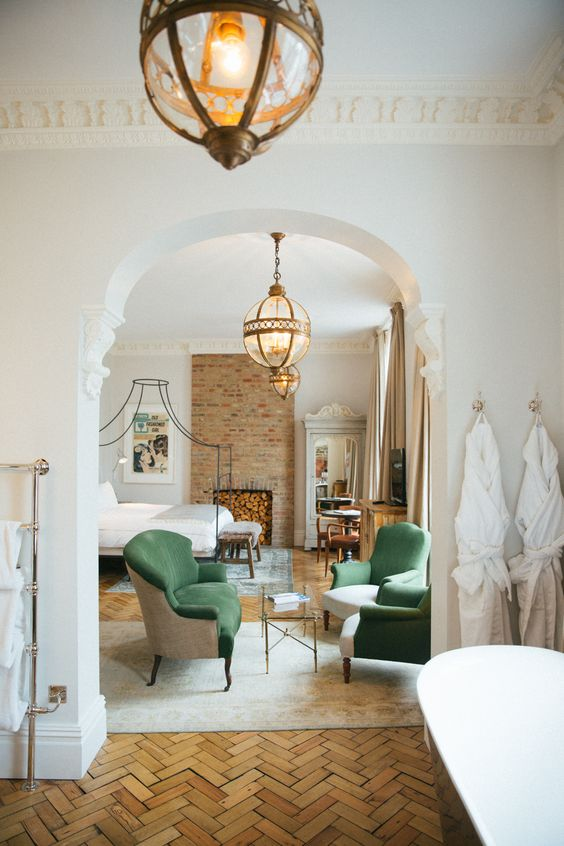 an arched doorway between the bedroom and bathroom highlights the refined style of the whole layout