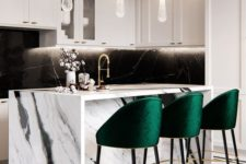 11 bold emerald stools with gold touches add color to the monochromatic kitchen and make the space cozier