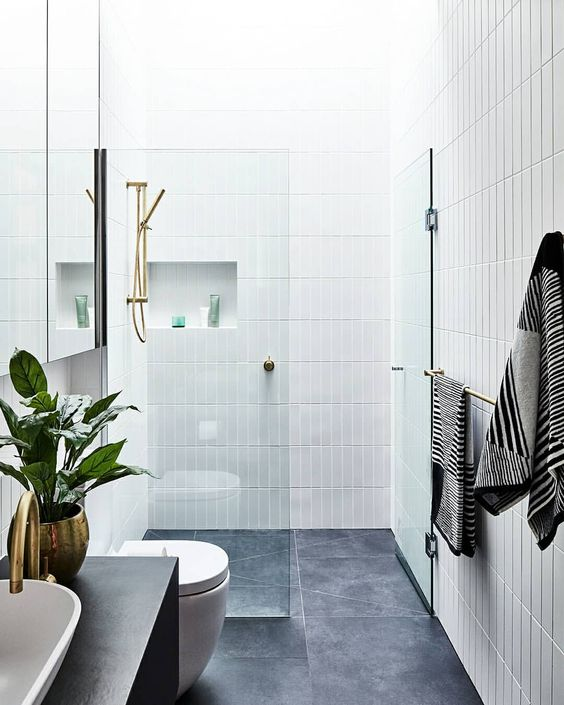 a chic contemporary bathroom with grey tiles on the floor and white skinny tiles on the walls plus niches