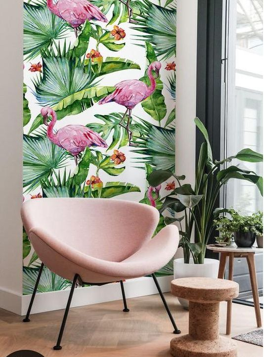 a cozy nook with pink flamingo print wallpaper, a blush chair, potted plants and a cork side table