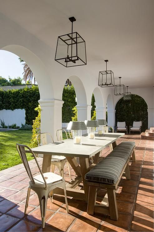 a cozy terrace with arched doorways and some comfy furniture brings in that elegant Spanish colonial style
