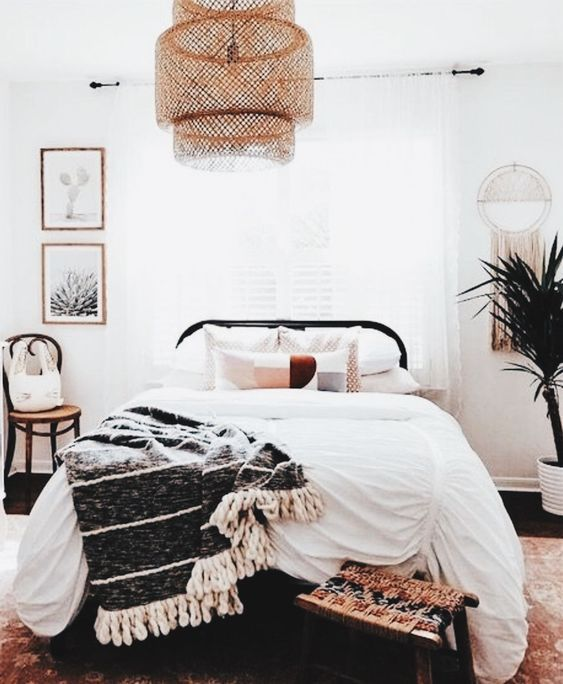 a welcoming boho bedroom with a large wicker lampshade over the bed that adds a boho feel to the space