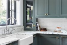 an elegant vintage green kitchen with skinny white tiles and marble countertops for a more refined and stylish look