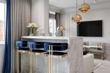 12 bright art deco stools with gold framing and navy touches highlight the elegant art deco style of the space