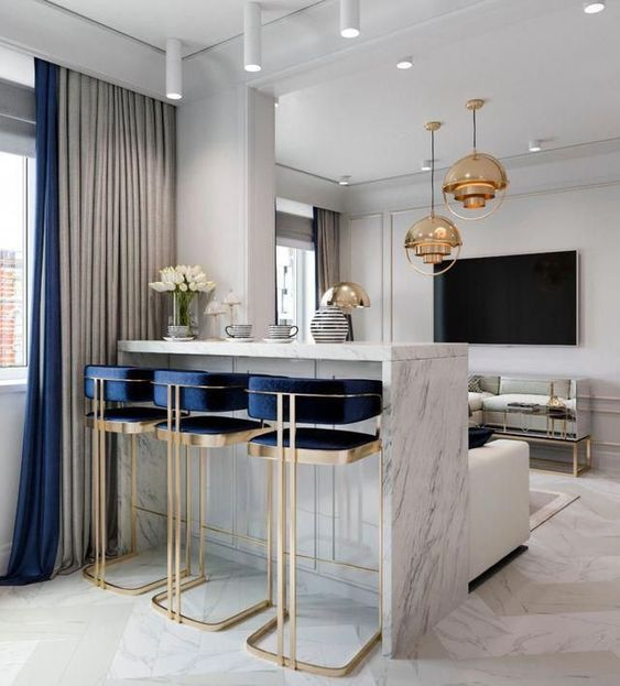 bright art deco stools with gold framing and navy touches highlight the elegant art deco style of the space