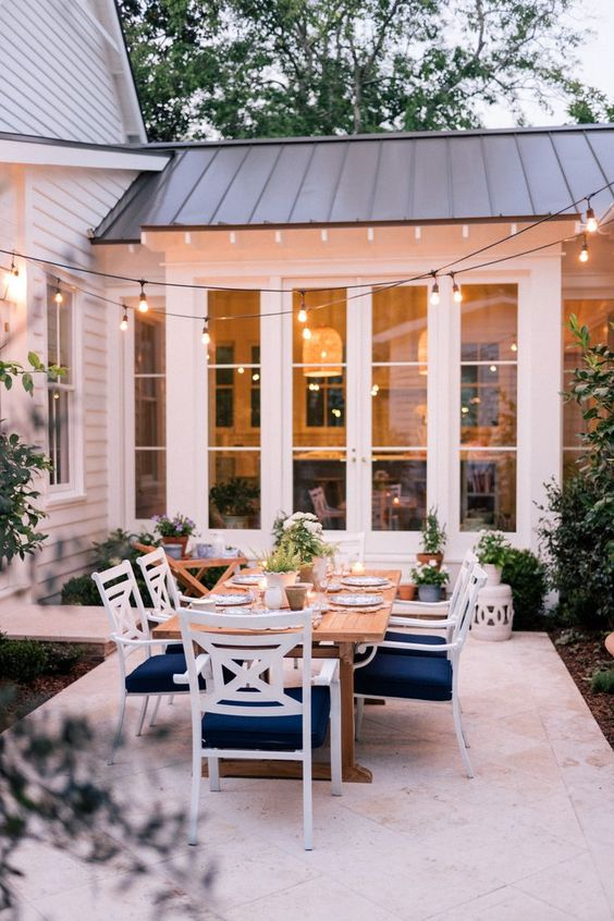 include a dining space into your patio with a table and white and navy chairs, spruce it up with potted plants