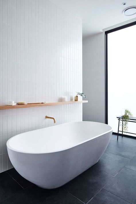 a chic minimalist bathroom with white skinny tiles on the wall and a white oval bathtub plus black tiles on the floor