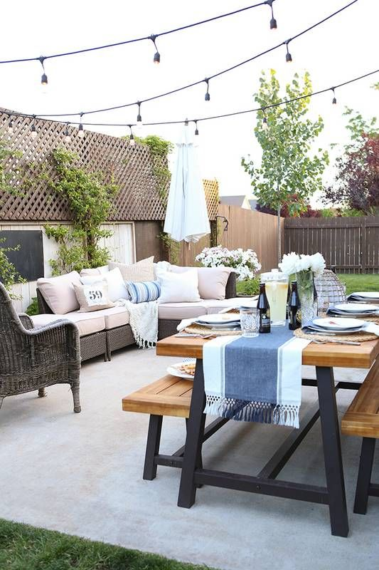 a patio seamlessly flowing into a dining space with a table and benches plus lights all over the space