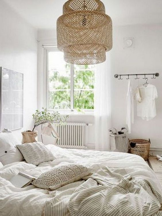 a welcoming neutral bedroom with a large wicker lamp over the bed that adds a natural feel to the space