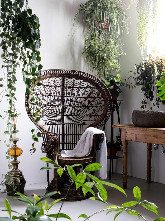 a dark stained peacock chair in a nook with potted greenery, a wodoen table and a Moroccan decoration for a boho feel