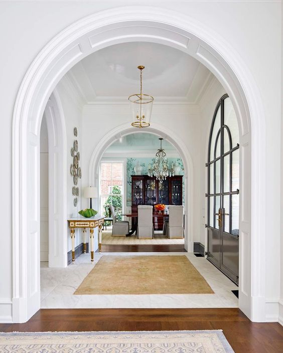 a very elegant and a bit formal entryway with arched doorways and arched doors for a refined look