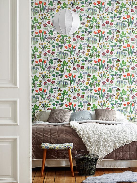 cheerful bright floral wallpaper on the statement wall make the bedroom more welcoming and summer like