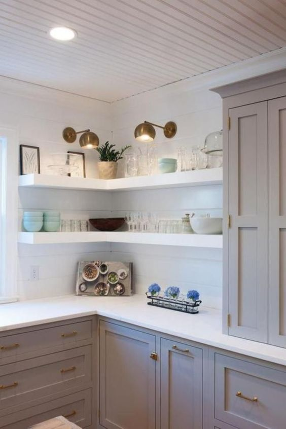 white thick corner shelves with additional spotlights are great to save some space in the kitchen